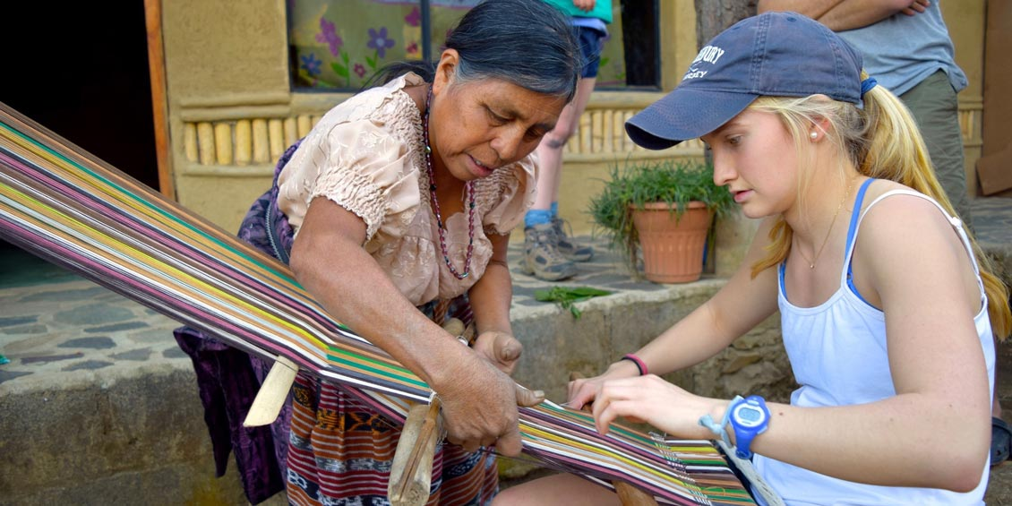 a student working with a woman using colorful threads