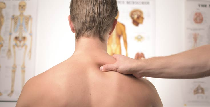 Shirtless man get his shoulder squeezed in front of medical poster