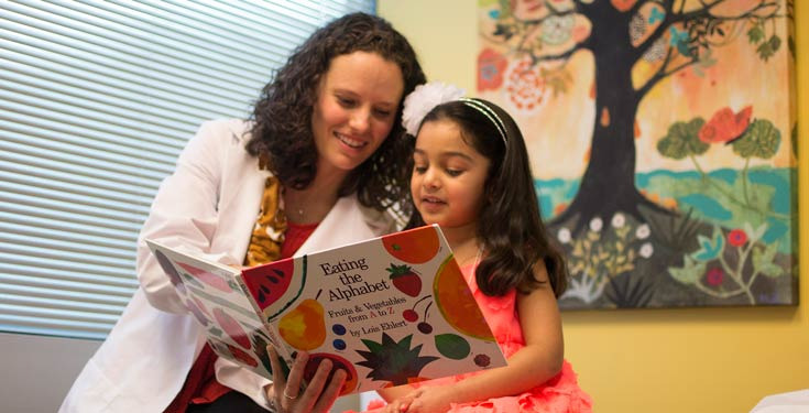 Woman in white coat reading eating the alphabet book to little girl