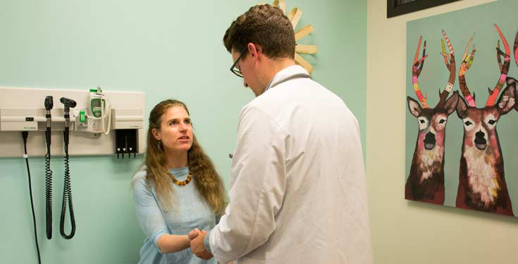 doctor checking woman's wrist