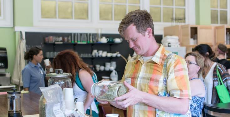 Smiling man holding jar of herbs