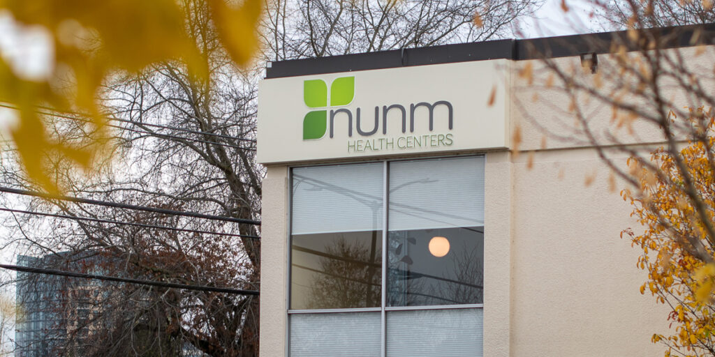 Exterior signage of the NUNM Lair Hill Health Center, which is located at 3025 SW Corbett Avenue, Portland, OR 97201.