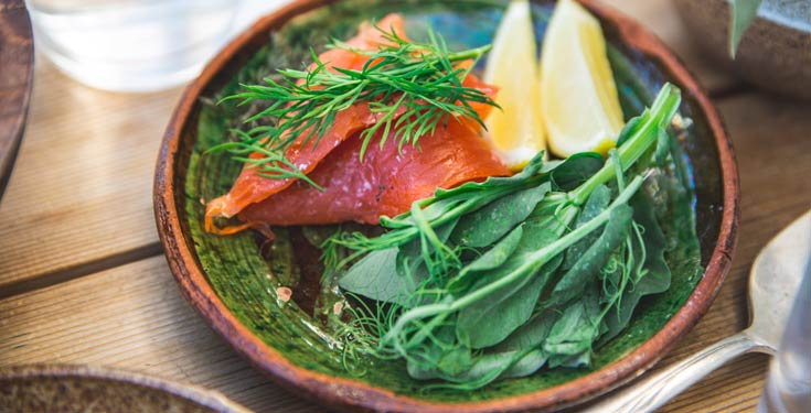 Salmon, greens, dill and lemons in a bowl