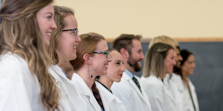 Smiling people in white coats