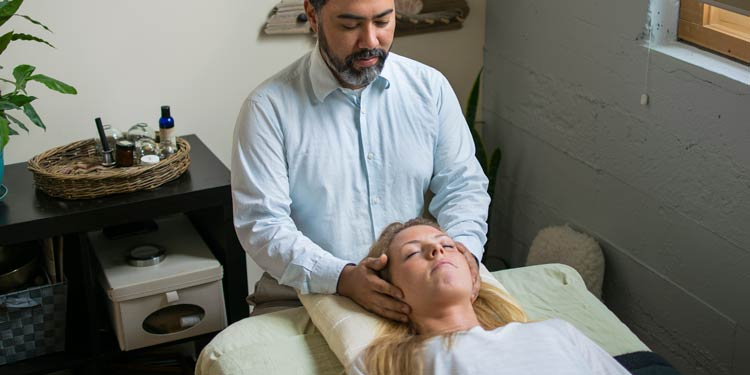 Acupuncturist holding patients head