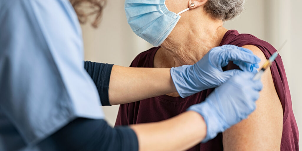 Healthcare practitioner vaccinates a patient in a clinic setting. Effective Oct. 18, 2021, or six (6) weeks after full FDA approval, whichever comes later, all Oregon healthcare providers will be required to be fully vaccinated against the COVID-19 virus.