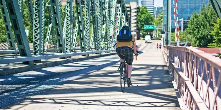 Person riding biking across bridge in Portland