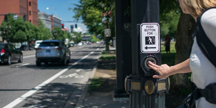 Women pressing a cross walk button at a street intersection in Portland